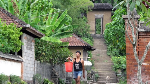 A man walking past traditional buildings in Bali