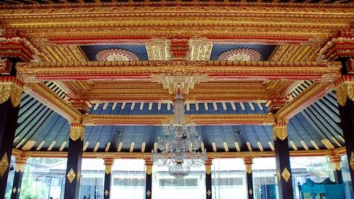 Ornate golden ceiling and chandelier of a Prambanan temple in Yogyakarta