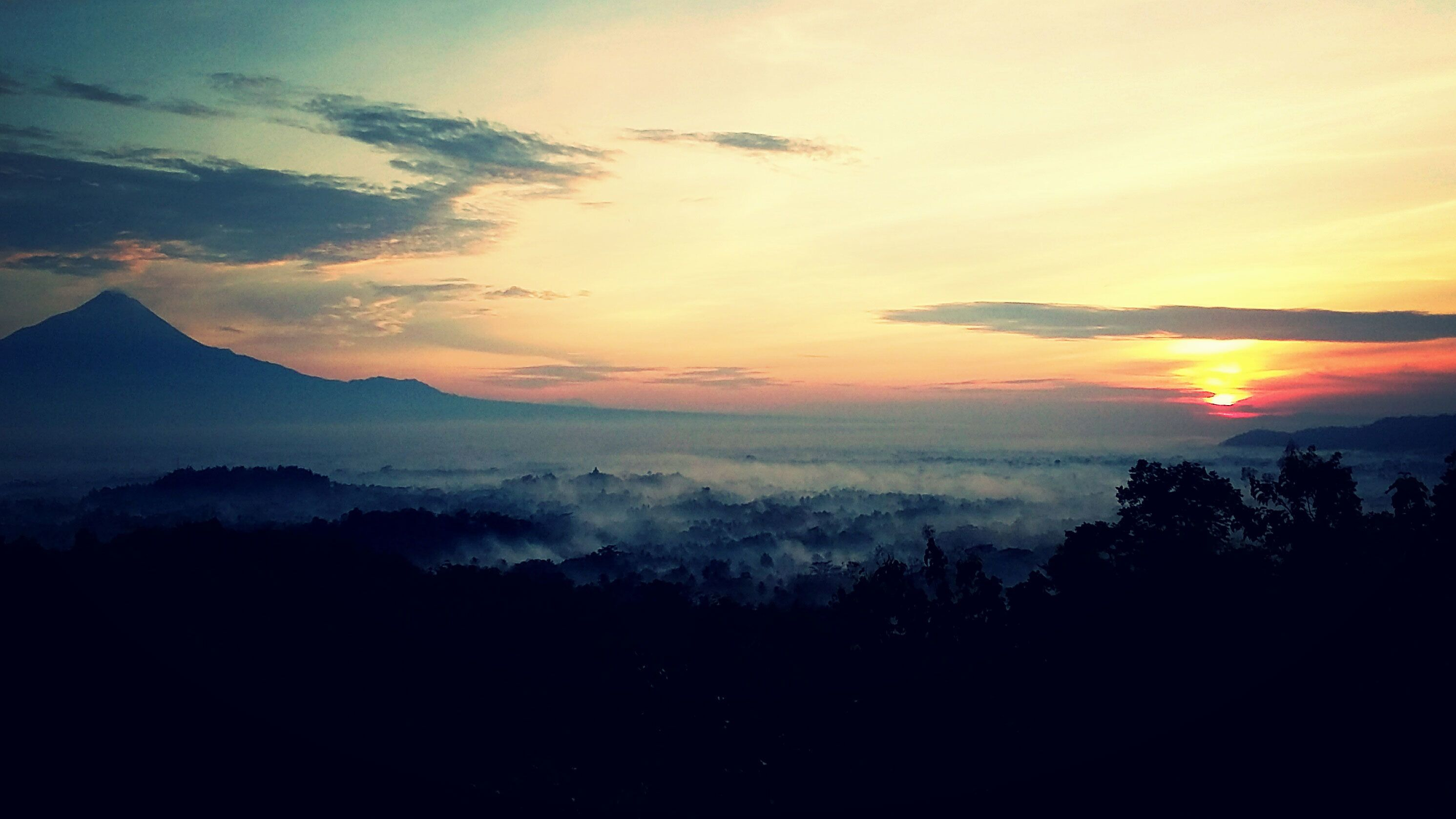 Early morning fog over the trees with mountains in the distance at sunrise in Yogyakarta