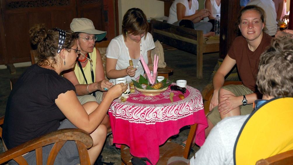 Show item 5 of 5. Tour group enjoying tea in Candirejo Village
