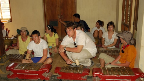 Tour group learning to play traditional instrumanets in Candirejo Village