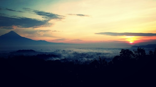Early morning fog among the trees with mountains in the background at sunset in Yogyakarta