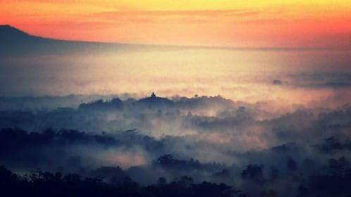 Fog surrounding Borobudur Temple as seen from a distance at sunrise in Yogyakarta