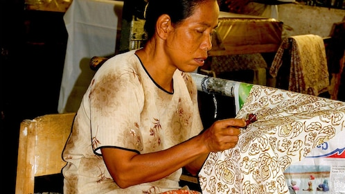 Batik craftswoman creating a pattern on fabric in Yogyakarta