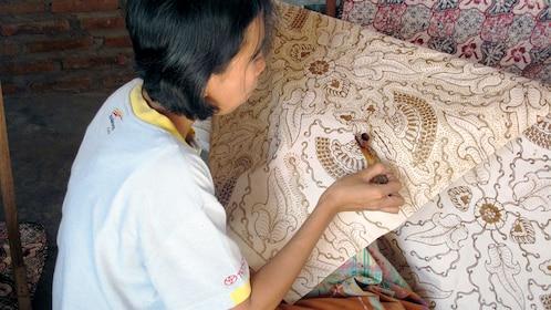 Batik craftswomen painting a pattern on fabric in Yogyakarta