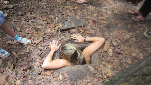 Woman climbing out of the Cu Chi Tunnels in Tay Ninh Vietnam