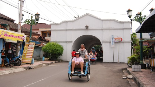 Cycle rickshaws going through town in Yogyakarta