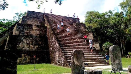 People walking up and down stairs of temple in ancient Mayan city of Tikal