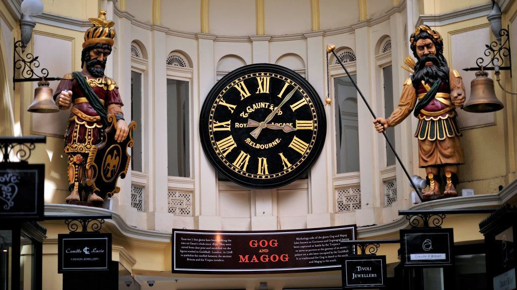 Big clock between two statues outside a building in Melbourn