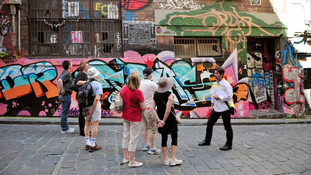 Show item 1 of 5. Visitors looking at street graffiti in Melbourne