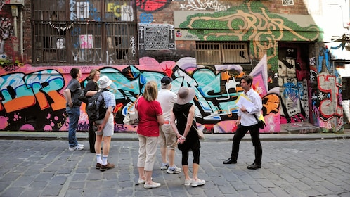 Visitors looking at street graffiti in Melbourne
