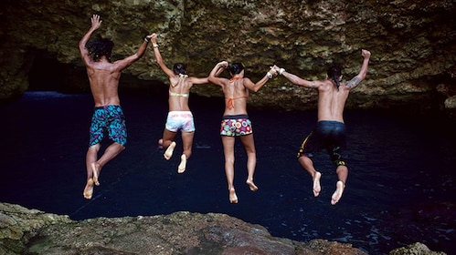 Group holding hands and jumping of a cliff into the waters of Grotto in Saipan