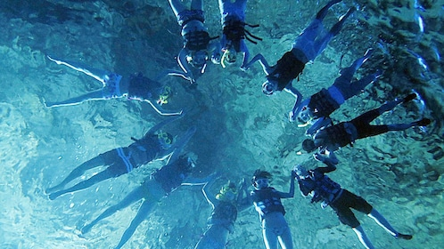 Group of snorkelers holding hand in the waters of Grotto in Saipan