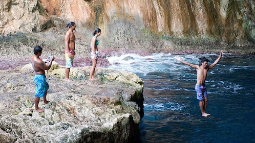 Group jumping off a rock cliff into the waters of Grotto in Saipan