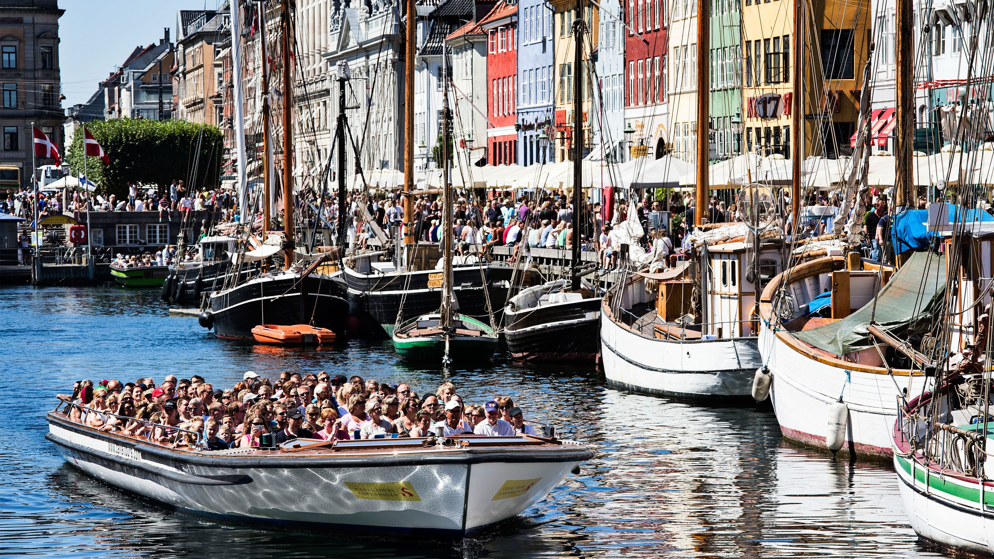 Boat full of people passing by a crowded street in Copenhagen