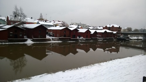 A view of snow covered homes lining a river in Porvoo