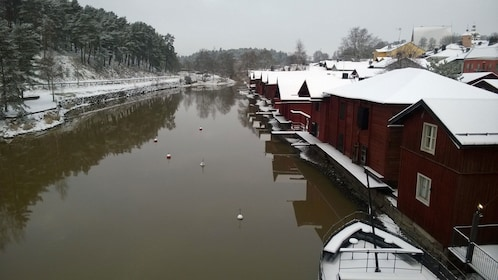 Snow covered buildings line a river in Porvoo