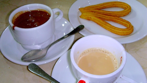 plate of hot chocolate and churro at Chocolate walking tour in Barcelona