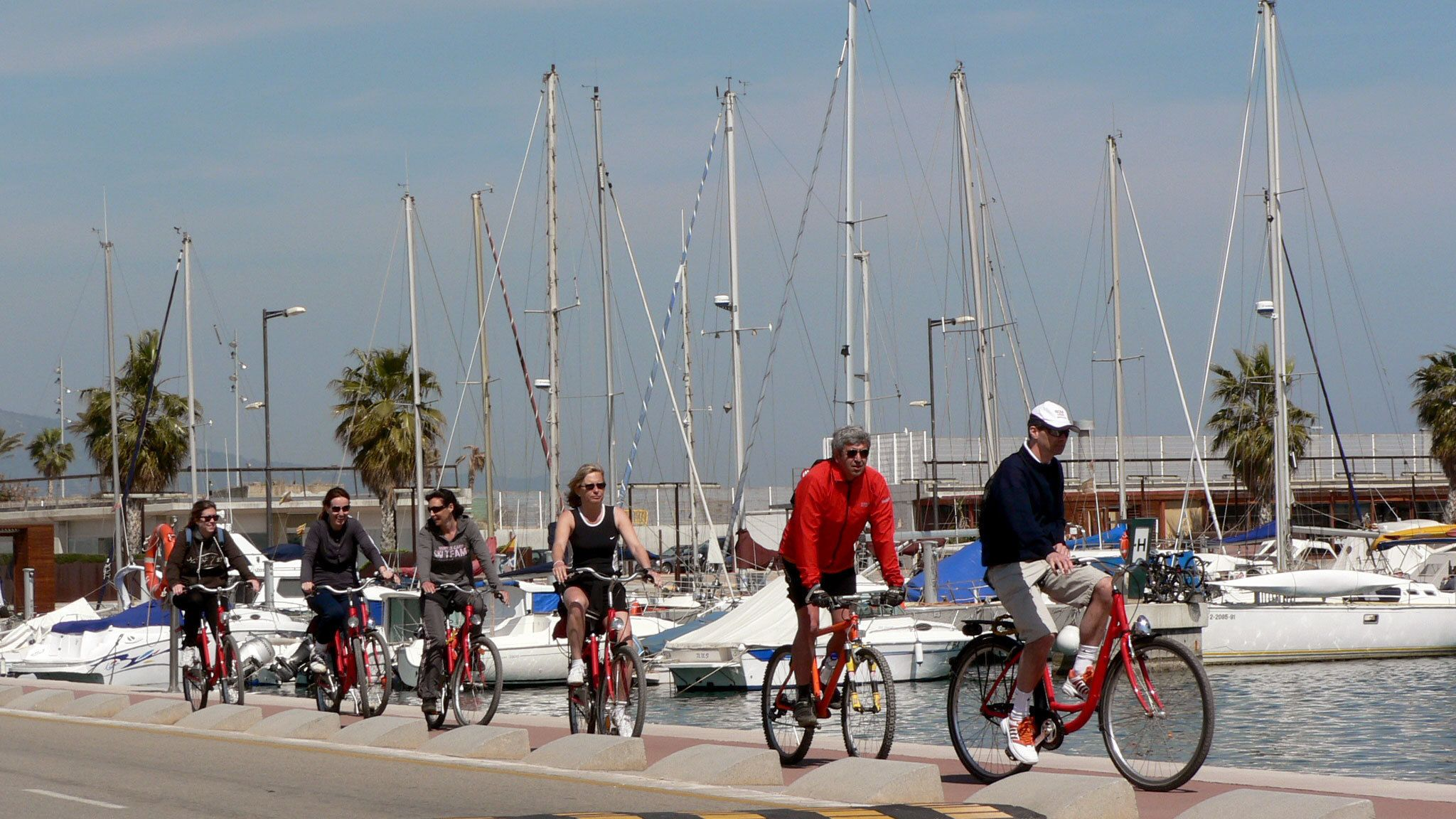 six people riding bikes by waterfront in Barcelona