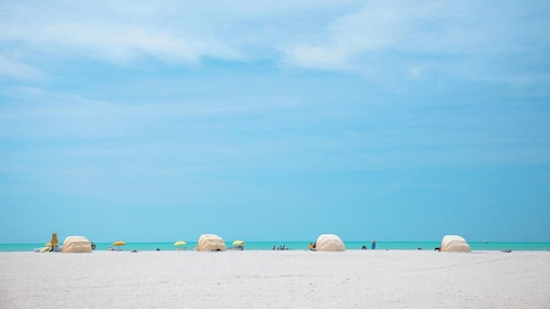 Wide white sandy beach with sun tents in Clearwater, Florida.