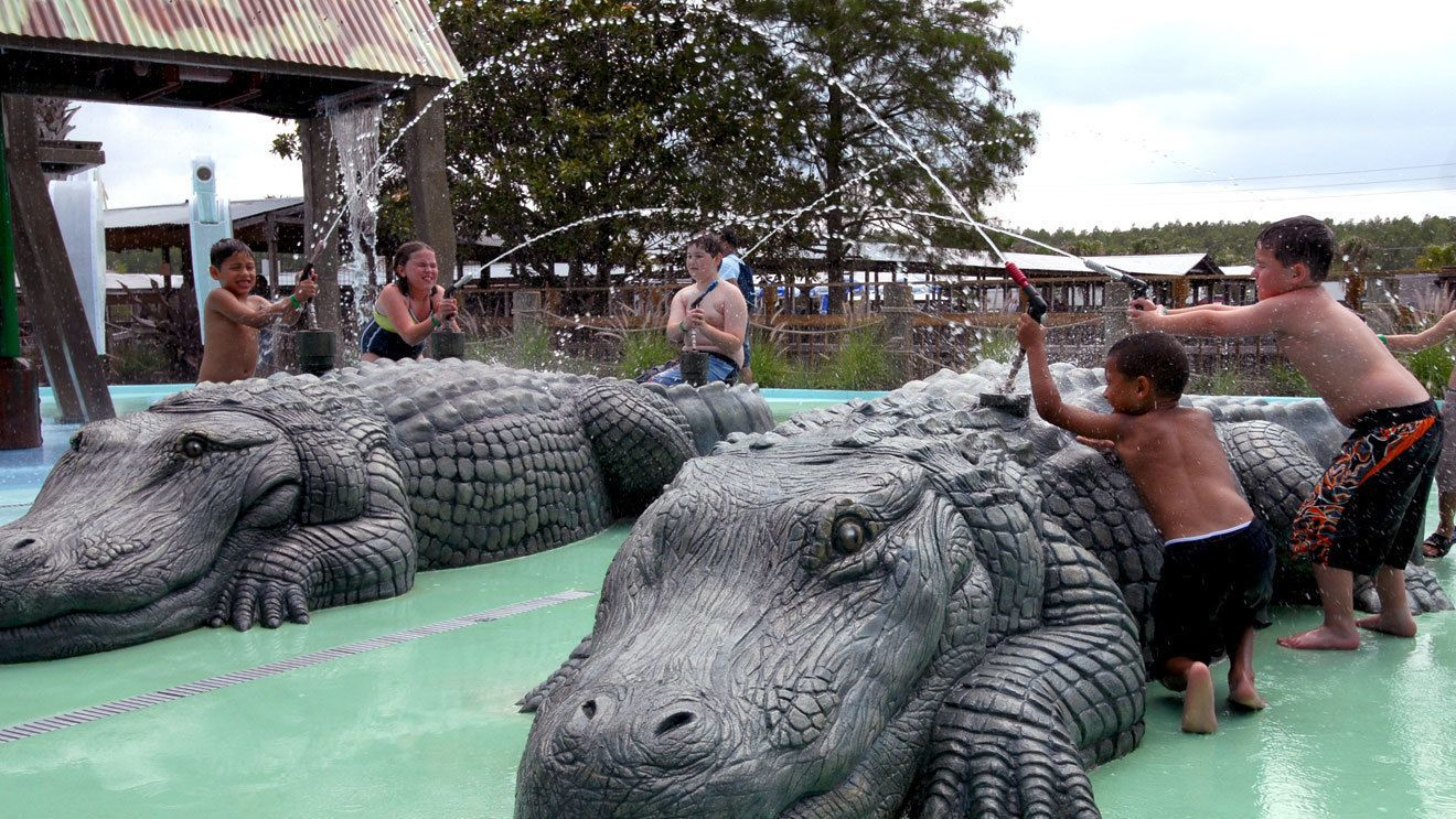 Water fight with kids in alligator-themed play area in Orlando.