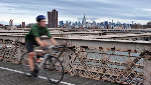Bicycling man on the Brooklyn Bridge with city in the background in New York