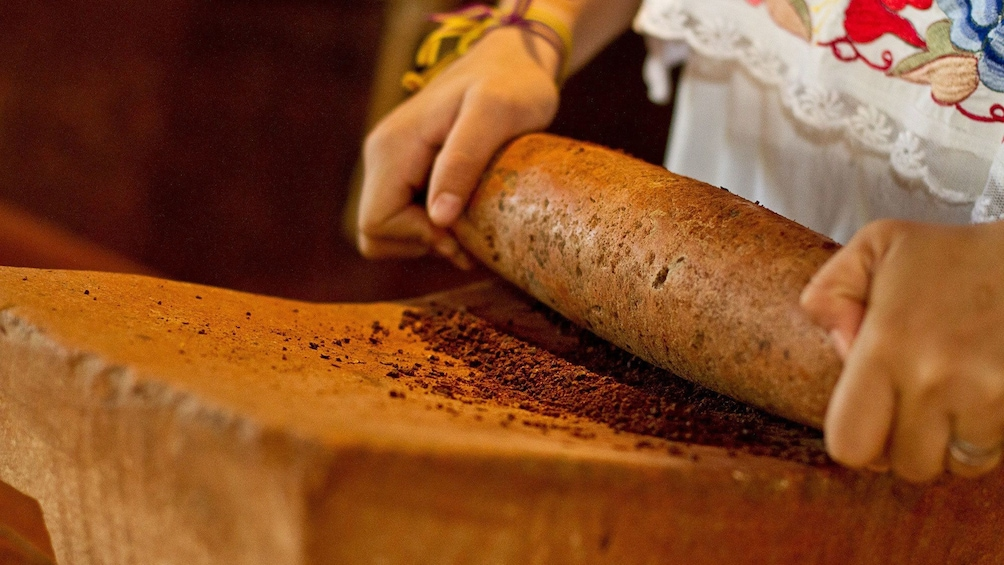 Show item 5 of 5. Woman grinding cocoa beans using traditional methods at the Choco-Story Museum in mexico
