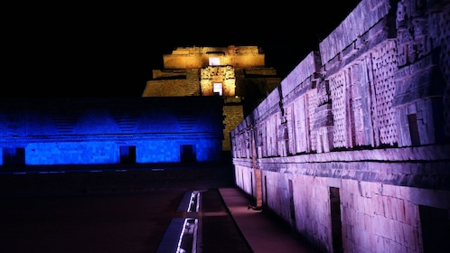 Remains of the Governor's palace and pyramid at Uxmal illuminated by colorful lights at night