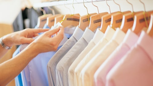 row of hangers with pastel colored collared shirts at store