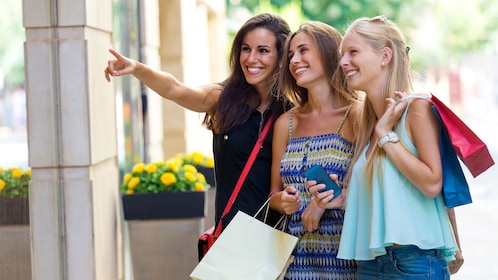 three smiling young ladies shopping at an outlet