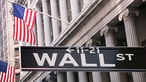 Wall Street sign with American flags in New York