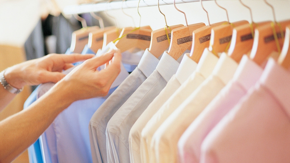 Show item 4 of 4. row of hangers with pastel colored collared shirts at store