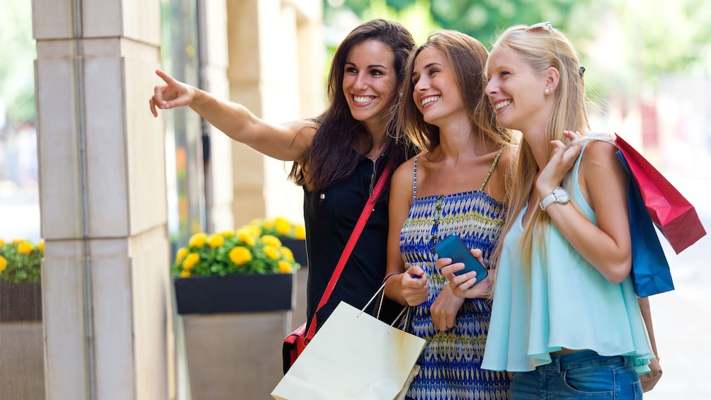 Show item 1 of 4. three smiling young ladies shopping at an outlet