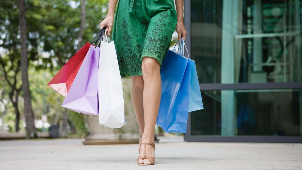 Show item 2 of 4. lady walking with five shopping bags at an outlet