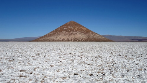Conical hill rising above the Salinas Grandes salt fields in Argentina