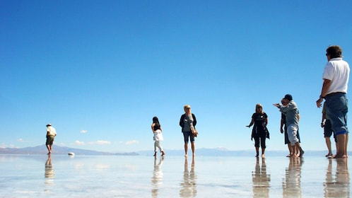 Tour group walking on the reflective surface of the Salinas Grandes salt fields in Argentina