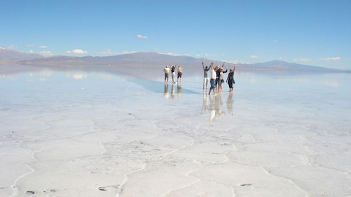 People walking on the salt fields of the Salinas Grandes with mountains in the background in Argentina