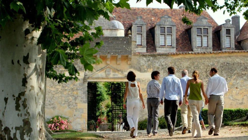 Foto 2 von 5 laden A tour group walking towards a historic building in  Saint Emilion