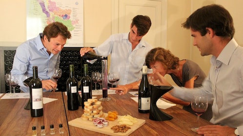 A small group of people examining different types of wine at the Saint-Émilion Vineyard