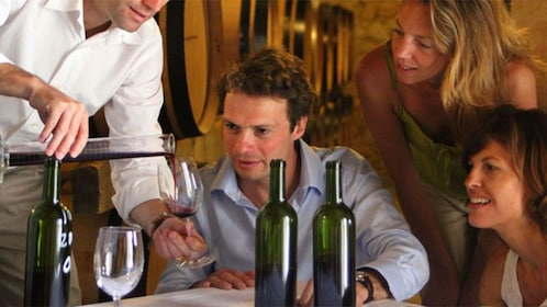 People tasting different red wines at a vineyard in France