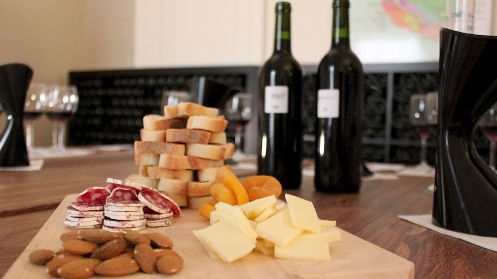 Charger l'élément 3 sur 5. an assortment of nuts meats and cheeses to go with different wines at a wine tasting class in France