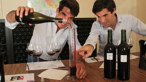 Two people decanting a red wine at a wine tasting class in France