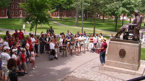 Harvard University tour guide with group at the statue of John Harvard in Boston