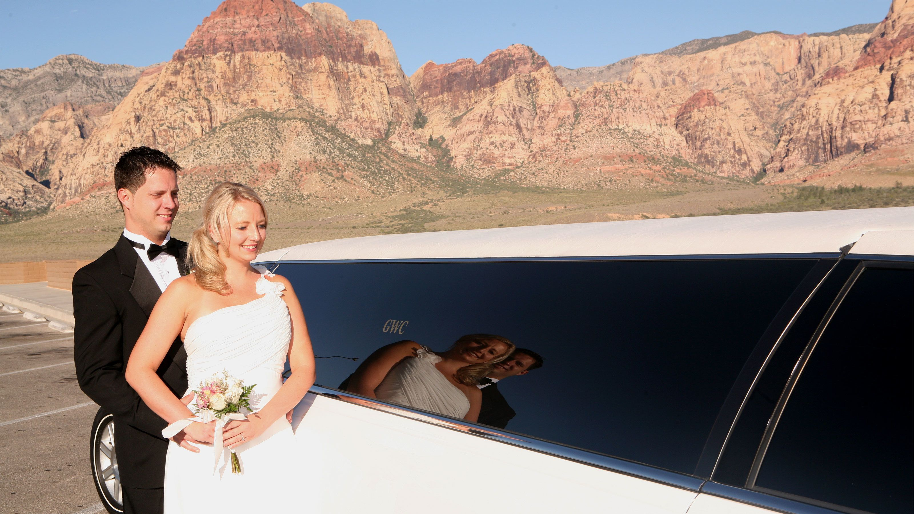 Happy bride and groom enter their limousine ready to depart from Red Rock Canyon