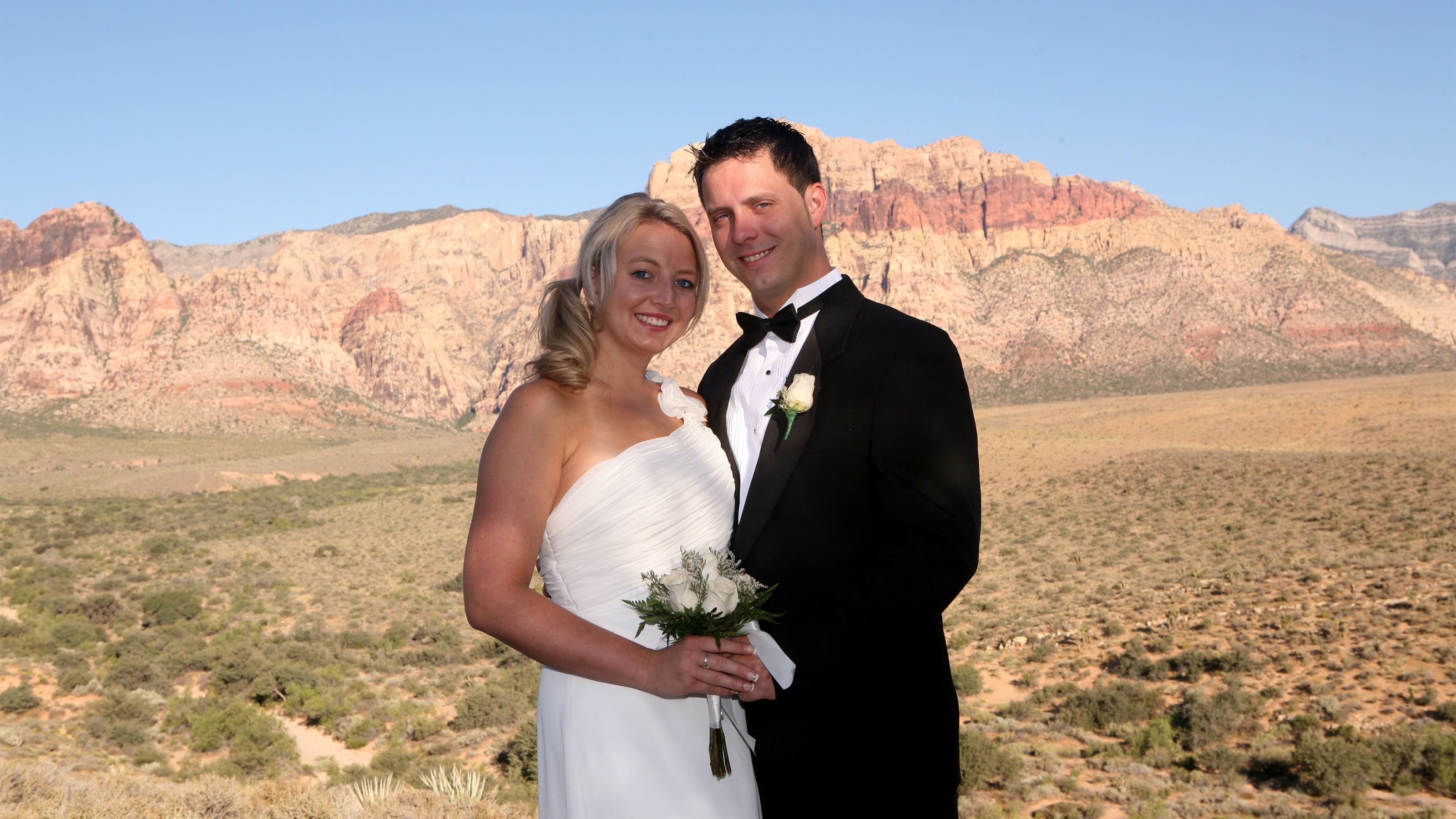 Beautiful bride and groom pose for a photo with the Red Rock Canyon in the background