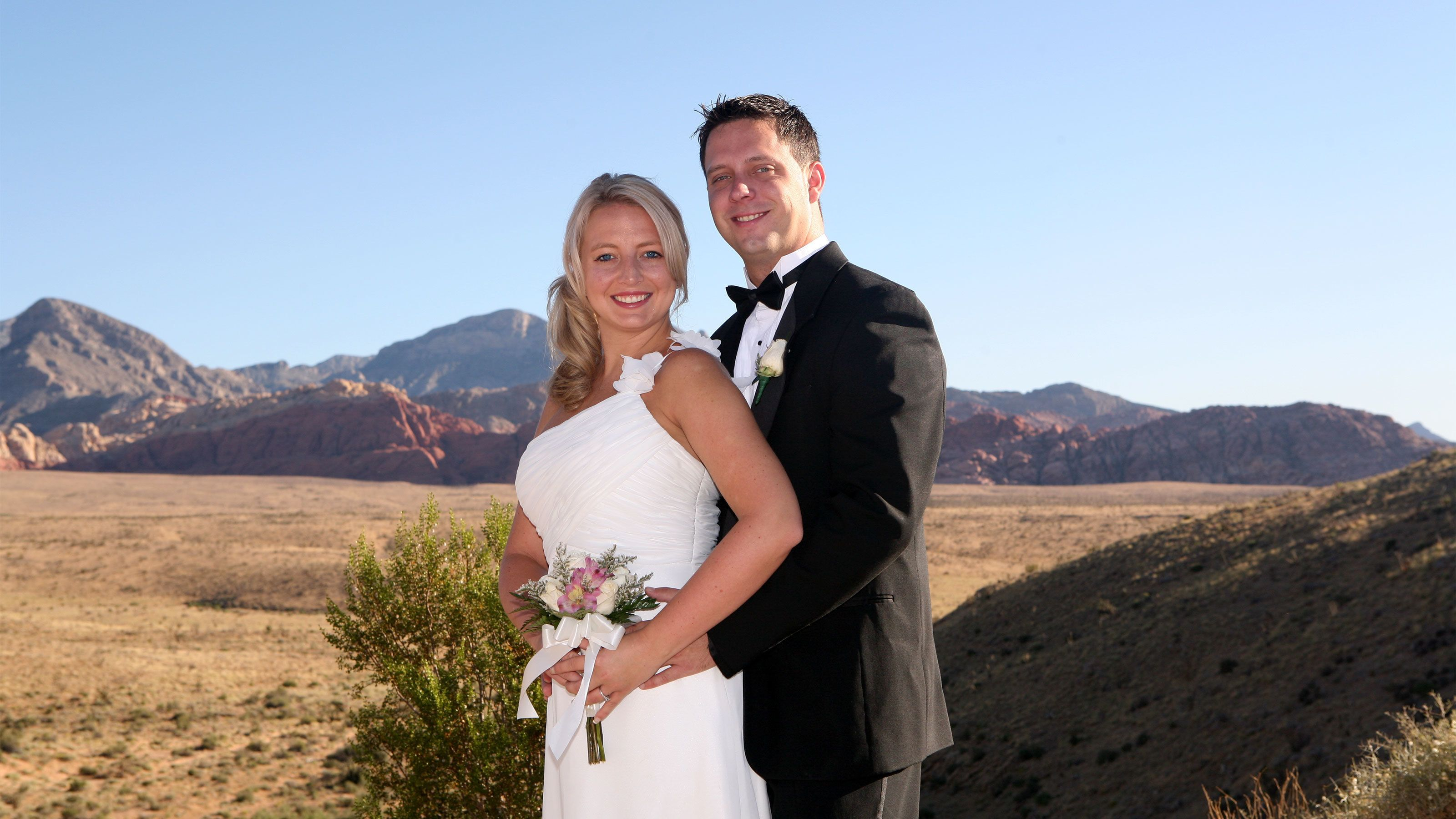 Lovely bride and groom pose for a photo with the Red Rock Canyon in the background