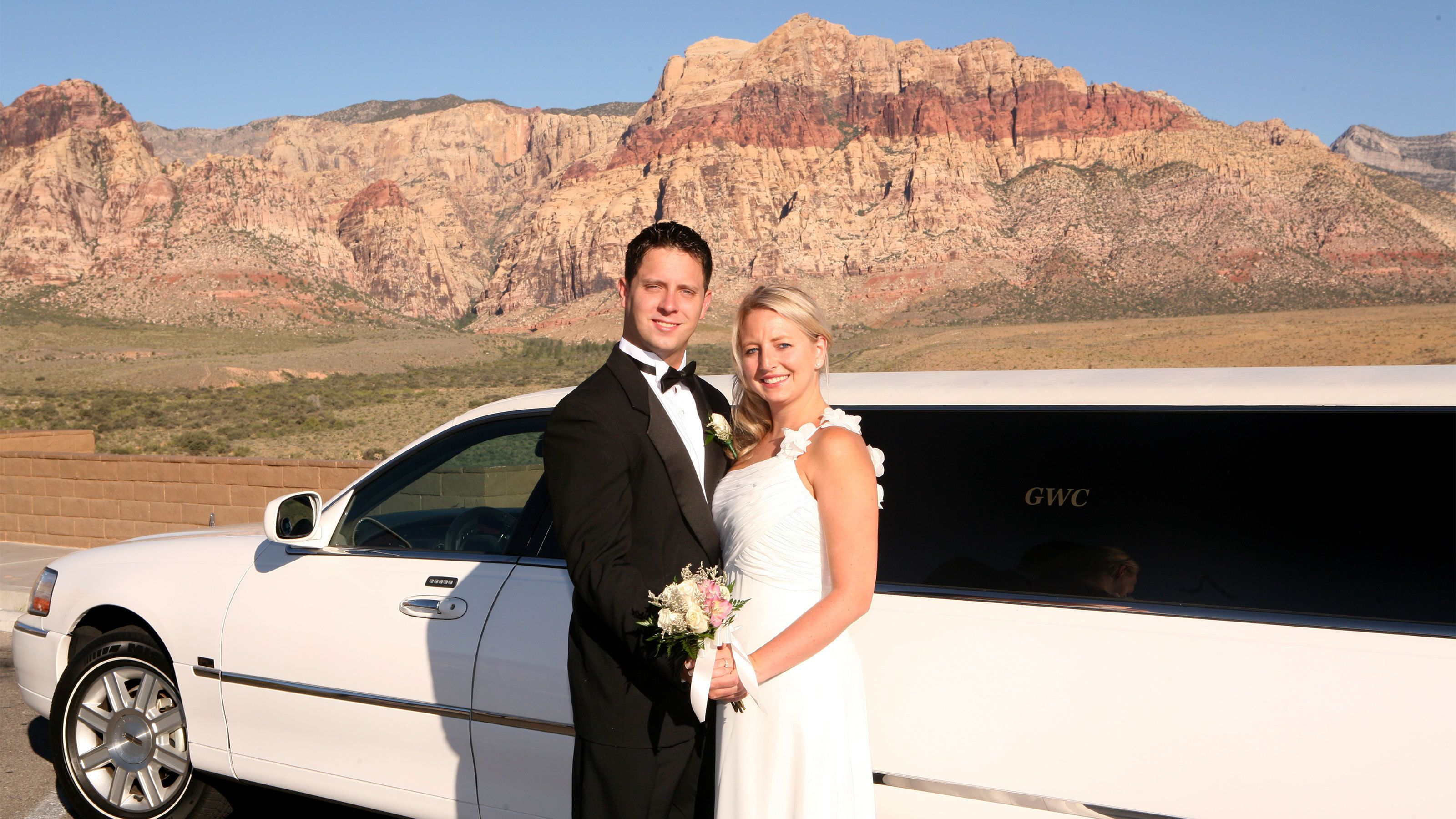 Happy bride and groom pose for a quick photo next to their limousine with the Red Rock