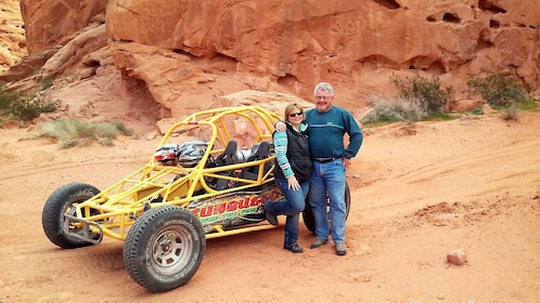 Couple standing in front of a dune buggy in the Nevada desert