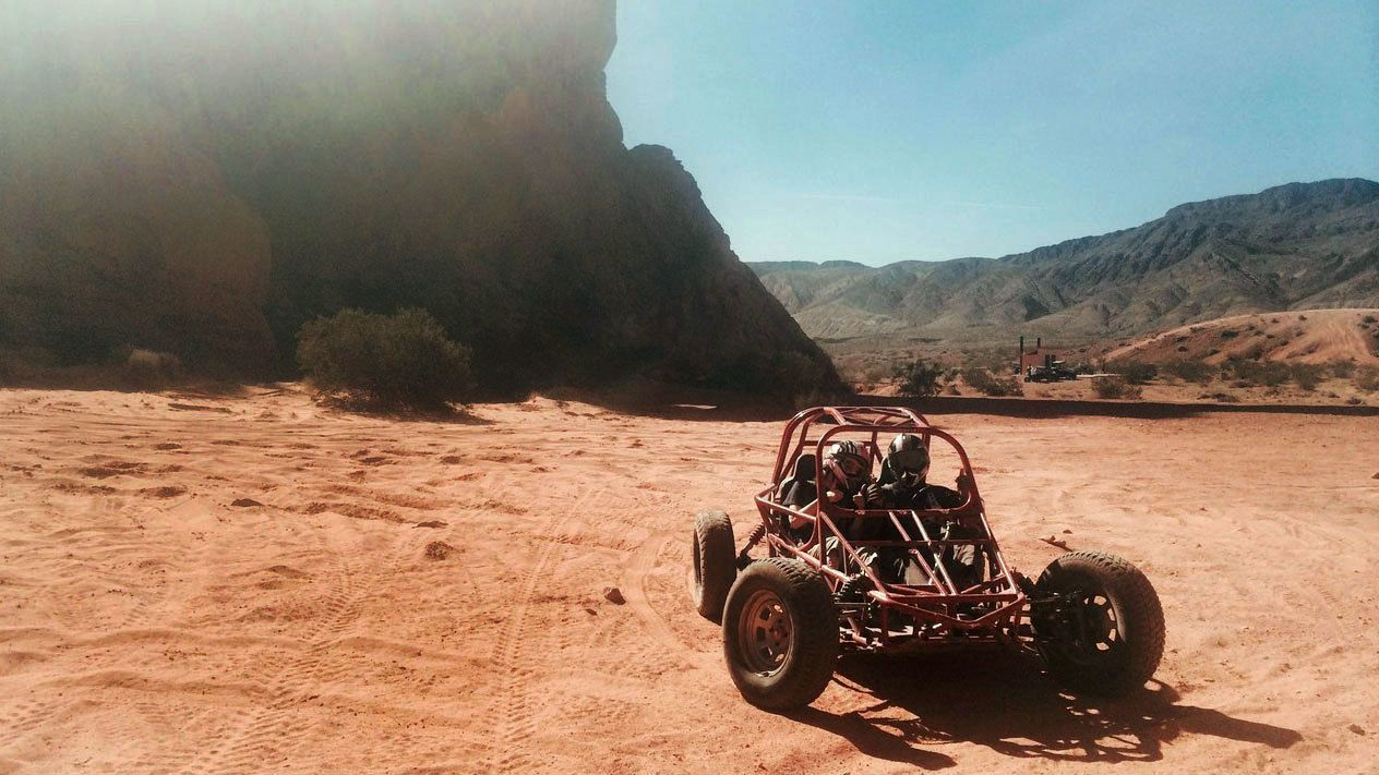 Driver and passenger on a dune buggy excursion in Nevada