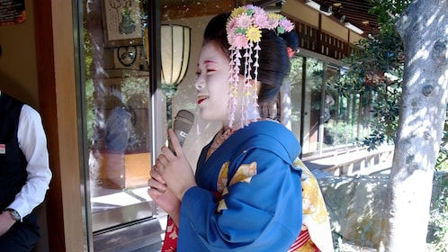 Woman in traditional outfit speaking on a microphone in Japan